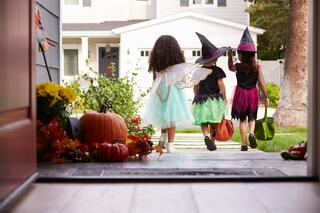 three children trick or treating in howard county on halloween
