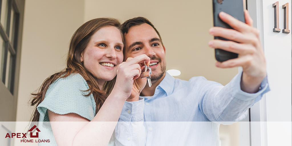 Couple taking selfie with keys to home
