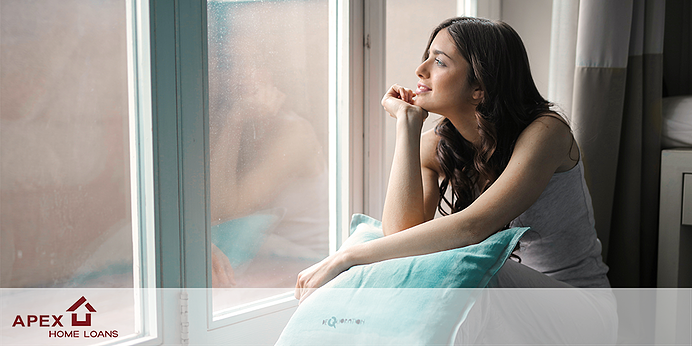 Melancholy woman looking out window